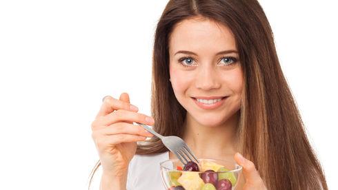 Femeie care ia micul dejun compus din fructe