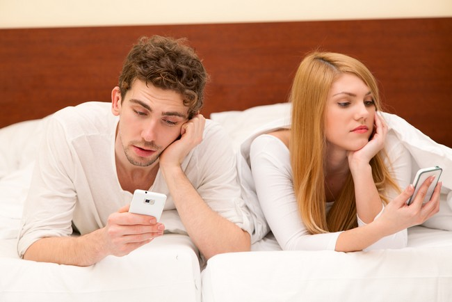 Young couple with smartphones in bed