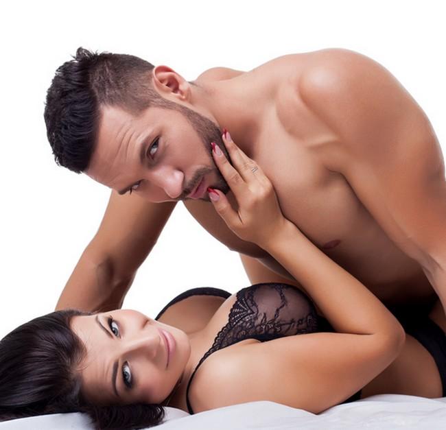 Beautiful lovers in bed posing at camera