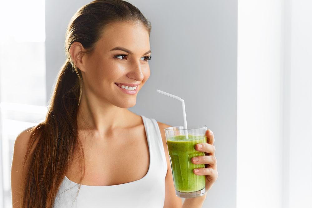 Femeie care bea un pahar cu smoothie verde