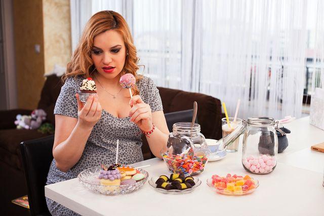 Femeie insarcinata care mananca multe dulciuri