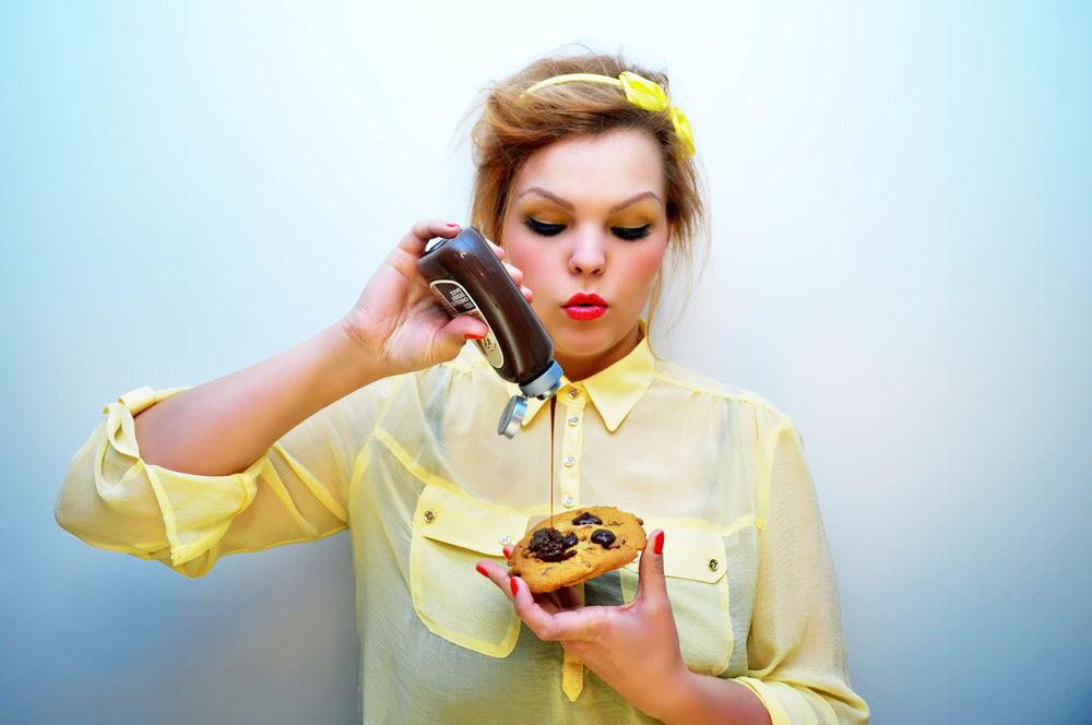 Femeie care mananca un fursec cu sos de ciocolata