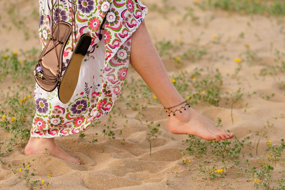 Femeie care se plimba in picioarele goale pe plaja