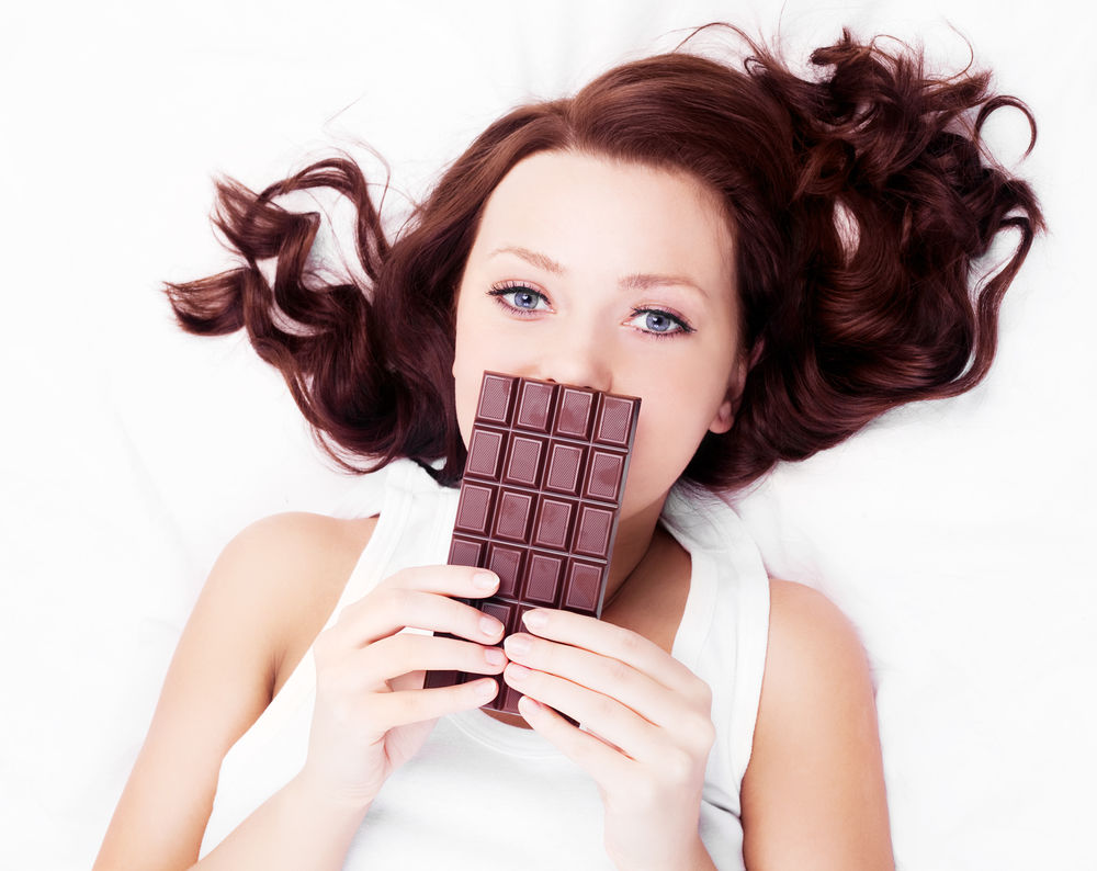 Femeie intinsa cu o tableta de ciocolata in mana